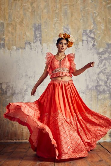 Scarlet printed Tussar lehenga teamed with trendy Frilled crop top with delicate hand embroidery & spiral organza dupatta