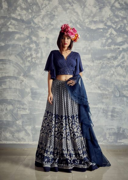 Midnight blue printed lehenga in natural fibre satin weave with chiffon pleated crop top with bell sleeves & mirror work teamed with frivolous organza dupatta