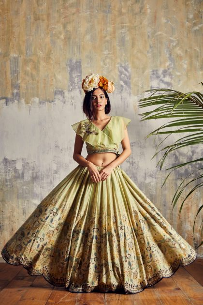 Soft lime Tussar lehenga with scallops teamed with hand embroidered wrap around crop top & spiral organza dupatta
