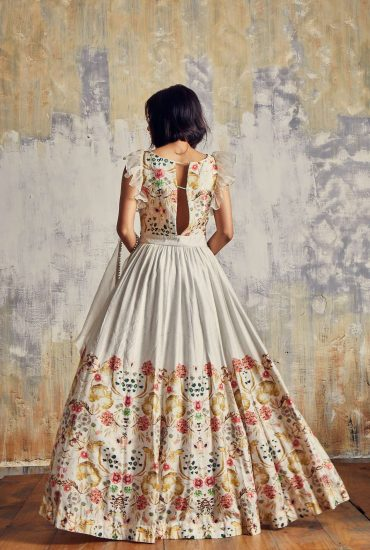 Timeless crème printed long dress in Tussar with beautifully hand embroidery neck line teamed with spiral organza dupatta