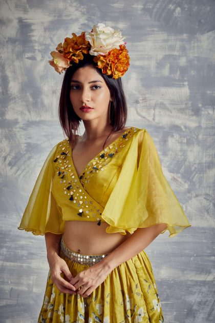 Pineapple yellow floral print flared skirt in linen satin teamed with hand embroidery trendy crop top & statement bell sleeves.