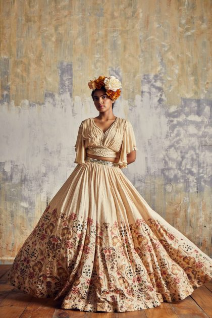 Almond cream printed Tussar lehenga with chiffon printed crop top and delicate mirror work with bell sleeves