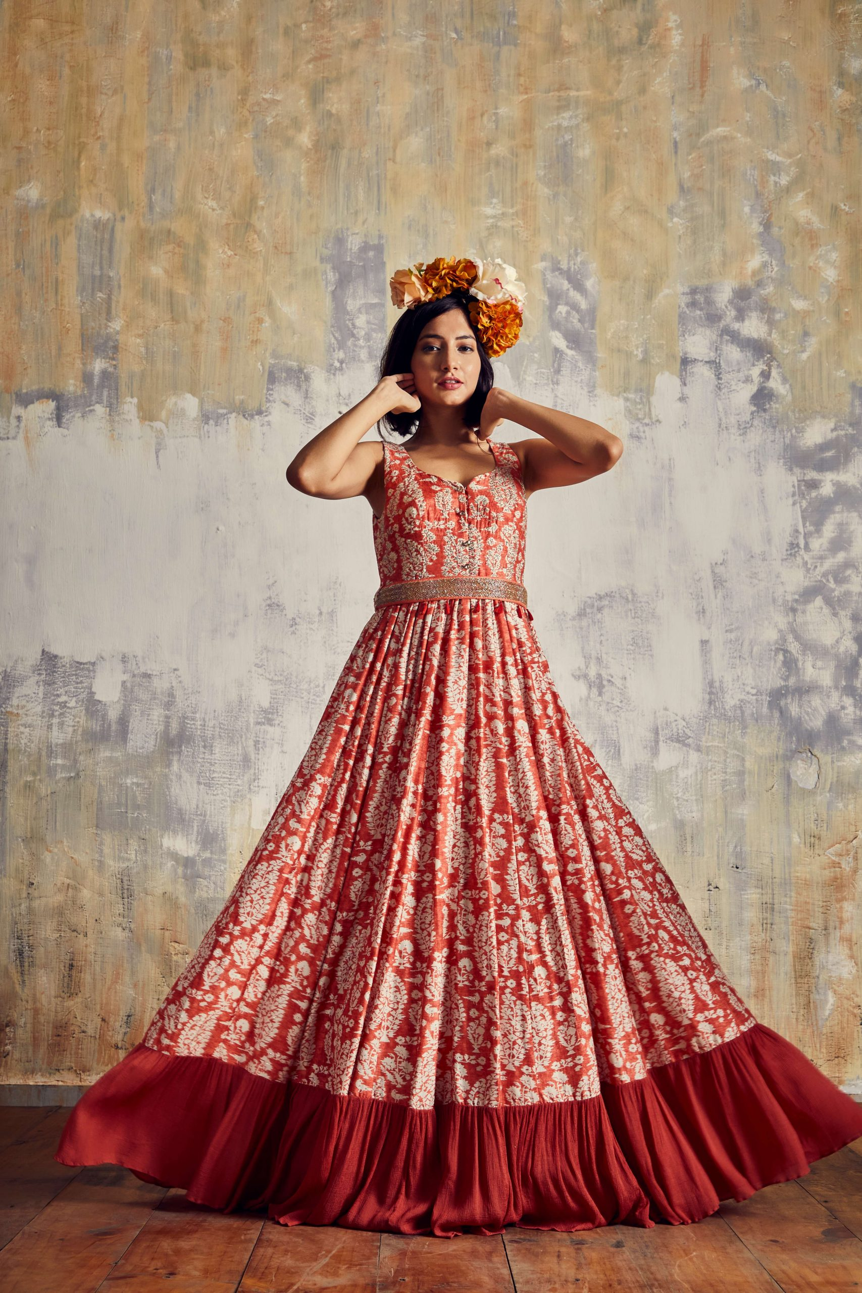 Trend setting Crimson red long dress in Tussar with embellished belt. The red chiffon frilled cut the bottom uplifts the style quotient.