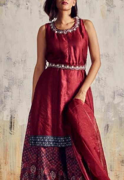 Maroon Mid length top with printed Sharara and delicate handwork on neckline & waist belt. Teamed with matching organza dupatta
