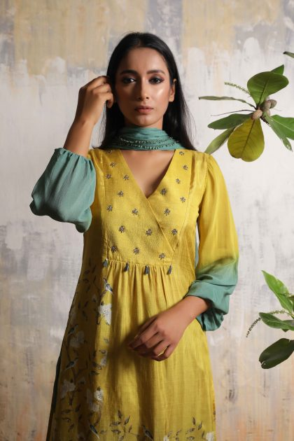 Corn yellow mid-length printed kurti in Tussar with Chiffon balloon sleeves and Chiffon lace dupatta and intricate handwork on yoke teamed with Teal green Chanderi crushed pallazos