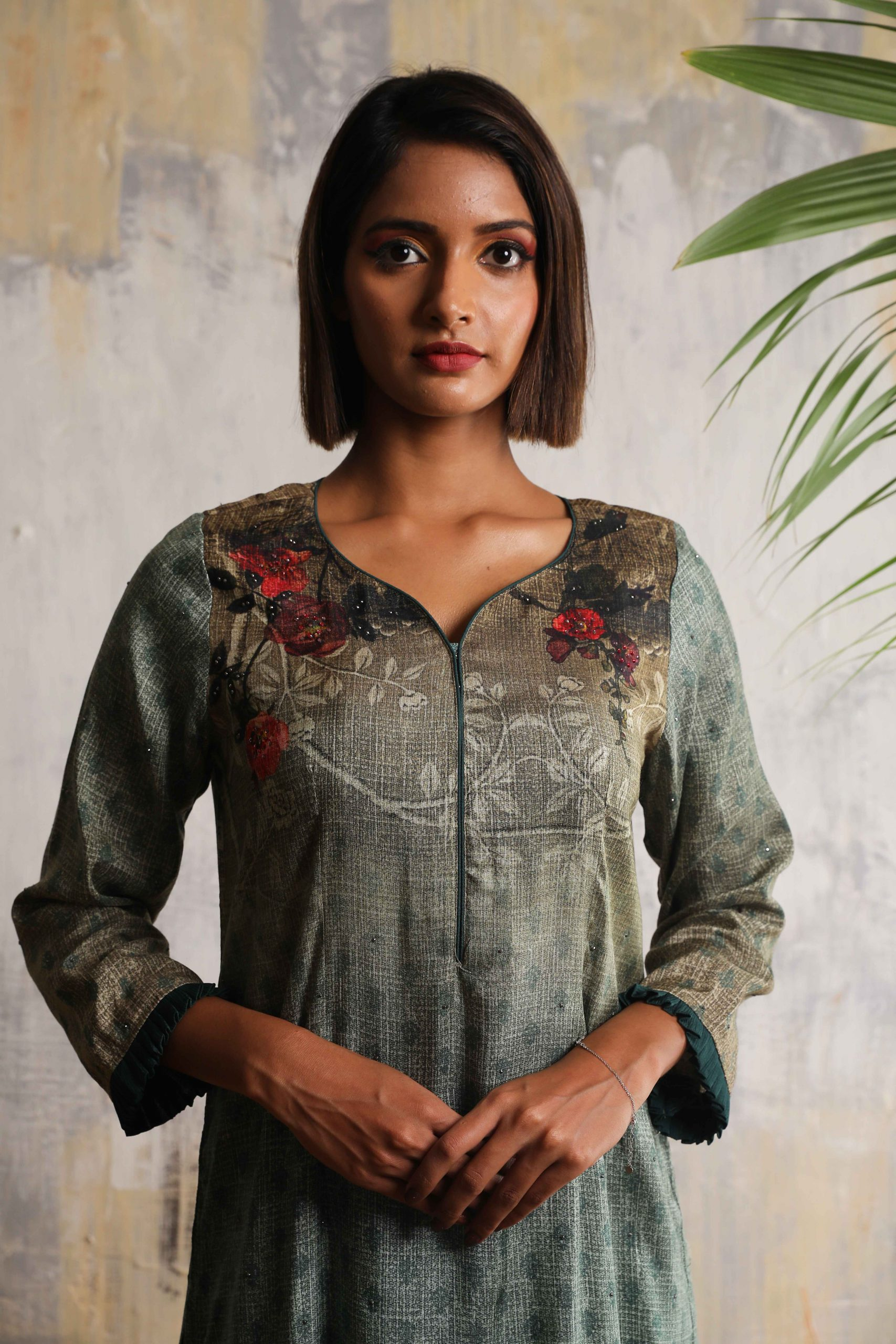 Teal green long printed A-line dress in Tussar with beautiful delicate hand embroidery neckline teamed with Bottle green Linen satin flared pants.