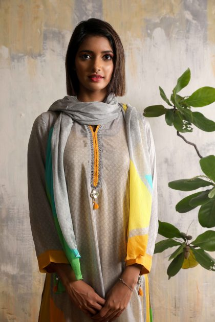 Artistically printed grey kurta in Crepe with detailed mirror work neckline and mustard crushed long slip dress in Russian Silk, teamed with smart matching scarf